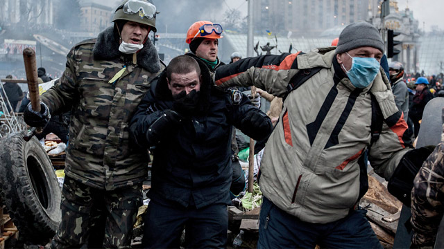 protesters on the Maidan have a policeman in their violence (Source: AP)