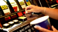 Hand wirft Münze in Spielautomat ein. (Quelle: Thinkstock by Getty-Images)