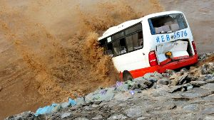An abandoned bus filled with sand bags is used to build a makeshift dike at a flooded area in Xingtai, Hebei Province