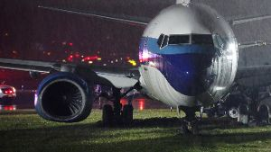 A campaign plane that had been carrying U.S. Republican vice presidential nominee Mike Pence rests in the grass after it skidded off the runway while landing in the rain at LaGuardia Airport in New York