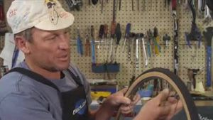 Lance Armstrong wechselt in skurrilem Video platte Reifen (Screenshot: Bit Projects)