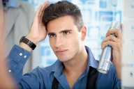 Man styling his hair in the mirror with hairspray (Quelle: Thinkstock by Getty-Images)