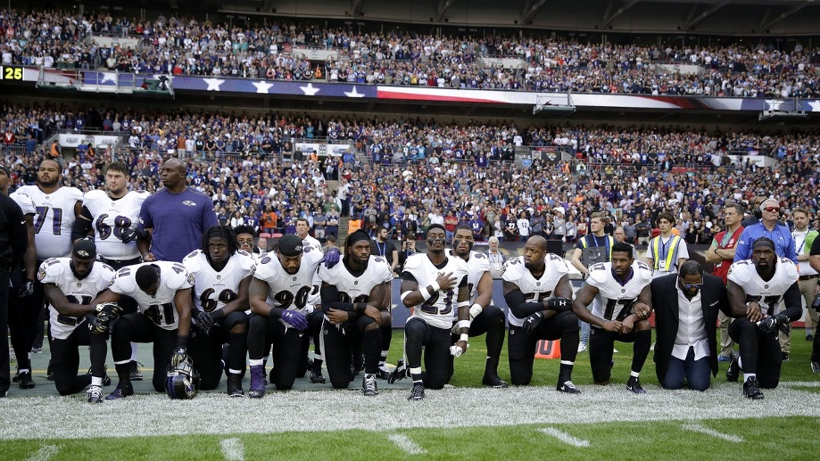 Spieler des Football-Teams Baltimore Ravens knien in London während der US-Nationalhymne aus Protest auf dem Rasen. (Quelle: dpa/Matt Dunham)