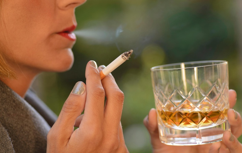 Woman drinking a glass of whiskey and smoking a cigarette. (Quelle: Getty Images/Buenaventuramariano)