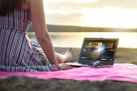 Eine Frau am Strand nutzt Video-Streaming auf dem Laptop: Immer mehr Windows 10-Rechner unterstützen Video-Streaming in HDR-Qualität. (Quelle: Thinkstock by Getty-Images/Tero Vesalainen)