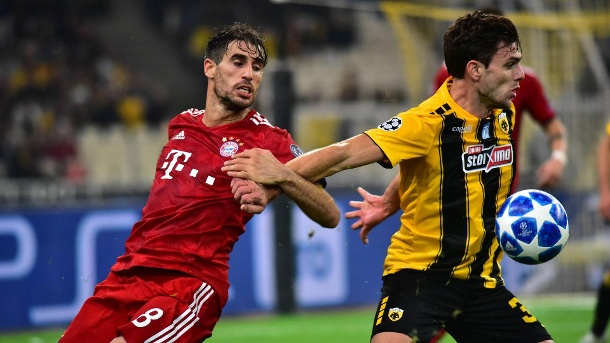 Champions League: AEK Athen muss Strafe an FC Bayern zahlen. Szene aus dem Hinspiel:  Javi Martinez (links) im Duell mit Athens Attiki. (Quelle: imago images/Pacific Press Agency)