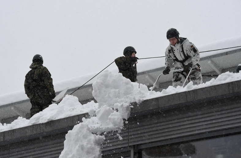 Soldiers of the German armed forces Bundeswehr remove snow from the roof of a high school building in Berchtesgaden (Quelle: Reuters/Andreas Gebert)