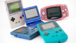 Verschieden Game-Boy-Versionen: Der erste Game Boy (l in Grau) erhielt über die Jahre etliche Nachfolger wie den Game Boy Pocket (blau, liegend), den Game Boy Advance SP (Mitte, aufgeklappt), den Game Boy Advance (r, rosa) und den Game Boy Color (vorne, mit Farbdisplay).