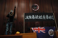 Besprühte Wände: Ein Demonstrant steht mit Megafon im Legislative Council, dem Parlament in Hongkong, vor vollgesprühten Wänden mit Forderungen an die Regierung. (Quelle: dpa/Kin Cheung/AP)