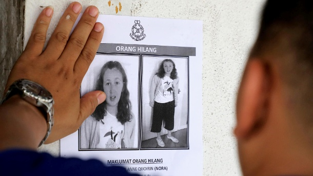A police officer paste a photo of 15-year-old Irish girl Nora Anne Quoirin who went missing from a resort on a wall at a shop in Seremban. (Quelle: Reuters/Reuters / Lim Huey Teng)