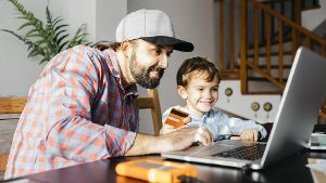 Father and son using laptop together online shopping model released Symbolfoto property released PU