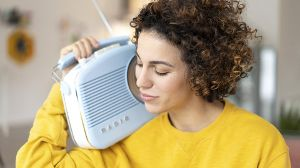 Woman listening to music with portable radio at home model released Symbolfoto property released PUB