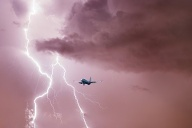Passenger airplane landing in the stormy weather on the backdrop lightning (Quelle: Getty Images/ FTiare)