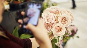 Close up of woman holding bunch of roses in flower shop taking a cell phone picture model released