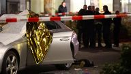 A body is seen near a damaged car after a shooting in Hanau near Frankfurt