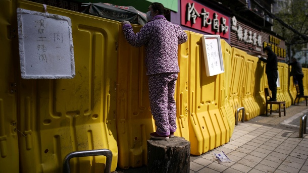 Residents pay for groceries by standing on chairs to peer over barriers set up to ring fence a wet market on a street in Wuhan (Quelle: Reuters/Reuters)