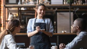 Attractive waitress laughing at African American man joke, serving customers