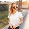 Young girl in trendy sunglasses and white polo shirt in a spring day at sunset (Quelle: Thinkstock by Getty-Images/Ales)