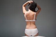 woman's back on grey background in lingerie (Quelle: Getty Images/antonmislawsky)