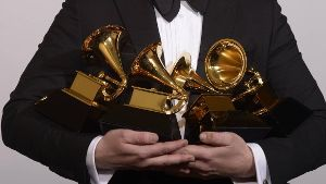 Sam Smith poses backstage with his awards for Record of the Year Best New Artist and Best Pop Vocal