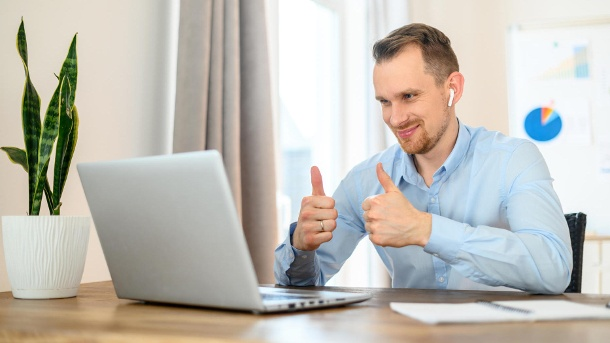 Guy in a formal shirt with airpods uses a laptop (Quelle: Thinkstock by Getty-Images)
