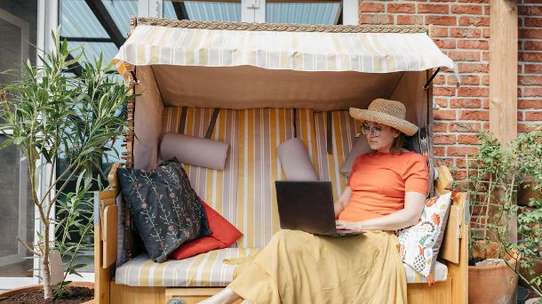 Mature woman sitting on terrace working on laptop (Quelle: Getty Images/Westend61)