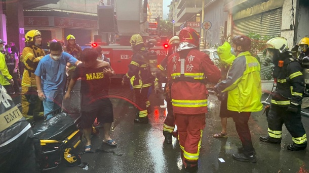 Firefighters and rescue workers stand in front of a skyscraper in the city center during fire fighting.  (Source: dpa / Handout / Fire Bureau Of Kaohsiun / ZUMA Press Wire)